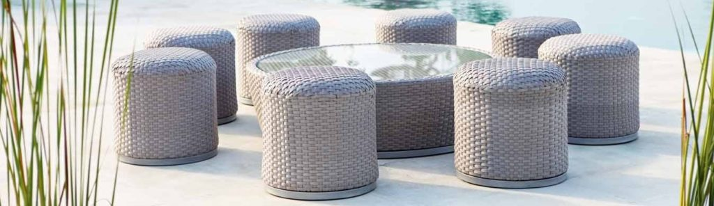 Eight grey rattan stools placed around a circular glass coffee table.