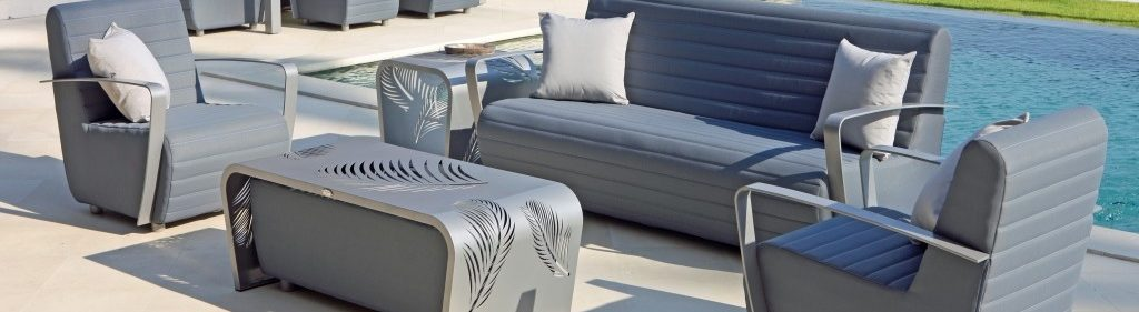 Set of grey rattan furniture, one two seater and two single seaters around a coffee table. They are placed next to a pool.