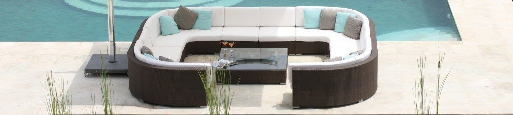 A large 'C' shaped sofa surrounding a glass coffee table. They are placed next to a swimming pool.