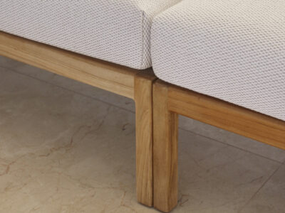 Close up on legs of two wooden chairs with white pillows