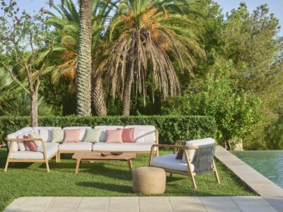 White corner outdoor sofa with single seater next to pool surrounded by palm trees