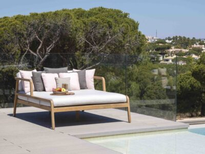 Large white day bed on balcony next to pool