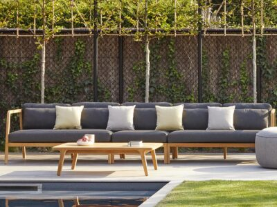 Long grey outdoor sofa next to pool with grey pouf and wooden coffee table