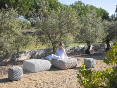 Female sitting on large grey poufs' on sand surrounded by trees