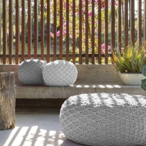 One large grey pouf with two small grey pouf sat on a wooden bench next to a white plant pot