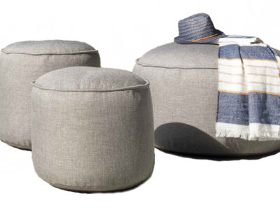Two small and one large grey pouf with a matching blue and white hat and scarf on
