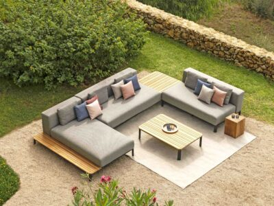 Grey outdoor corner sofa surrounded by green bushes and pink flowers