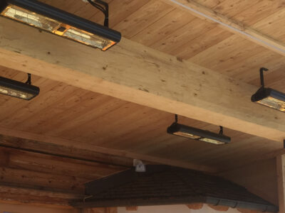 Outdoor heaters attached to outdoor wooden roof