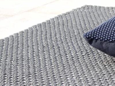 Grey outdoor rug laid down next to pool with grey pillows on top