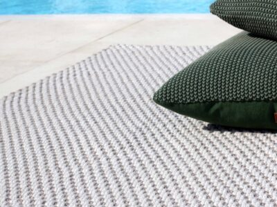 Grey outdoor rug laid down next to pool with green pillows on top