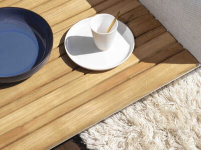 Corner of wooden coffee table with white cup and saucer on