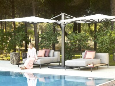 Female sat on one of two grey sun loungers with pink cushions on next to pool