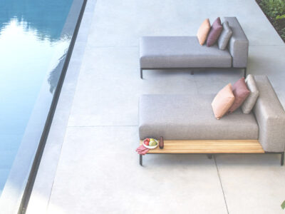Two grey sun loungers with pink cushions on next to pool