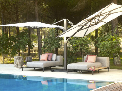 Large grey sun loungers around a pool with large parasols above them