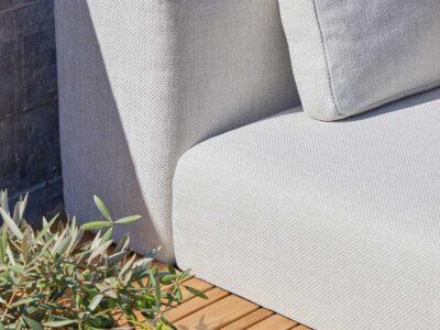 Corner of grey outdoor sofa.