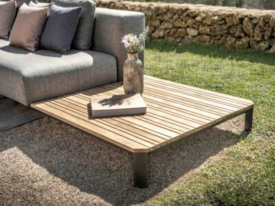 Wooden side table with vase and book on. The table sits next to a grey outdoor sofa with purple and grey cushions on.