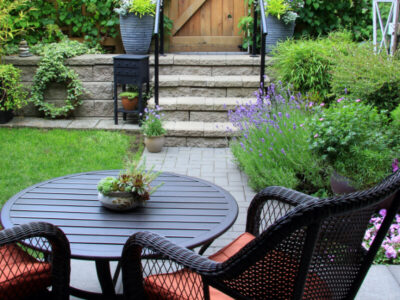 Black and orange outdoor chairs in garden with pink flowers in pots and a small concrete staircase