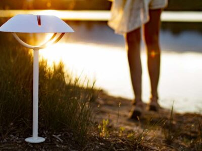 Female walking towards lake with sunlight beaming onto small white lamp post