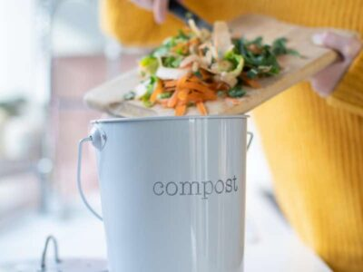Female using knife to put vegetable waste into pot labelled 'compost'